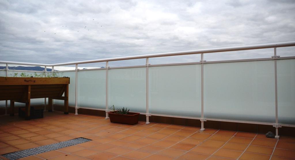 Instalación de barandilla de aluminio lacada en blanco y cristal de seguridad seda en un ático de Huesca.